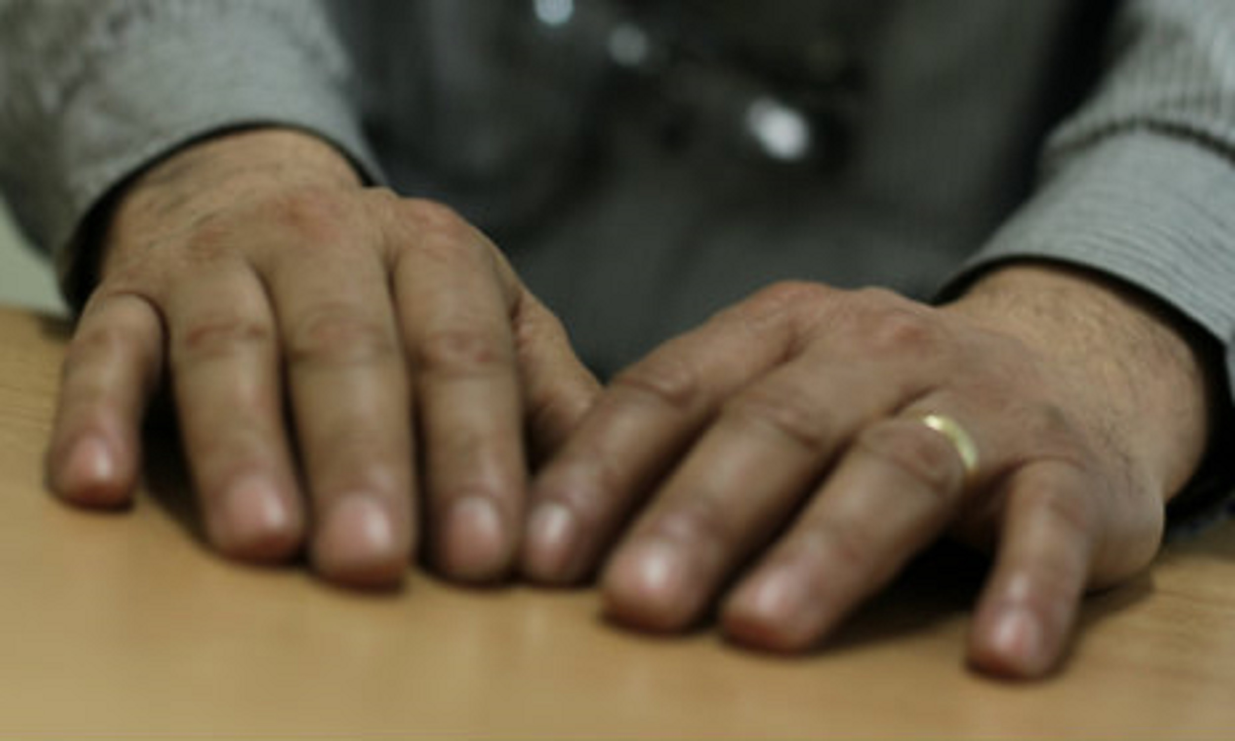 Photo of man's hands on table top