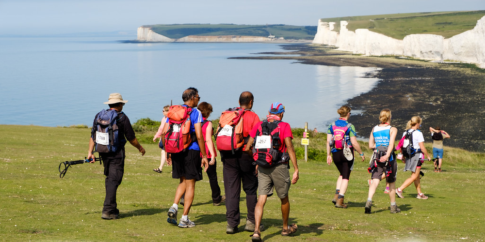 a group of people trekking next to a white cliff