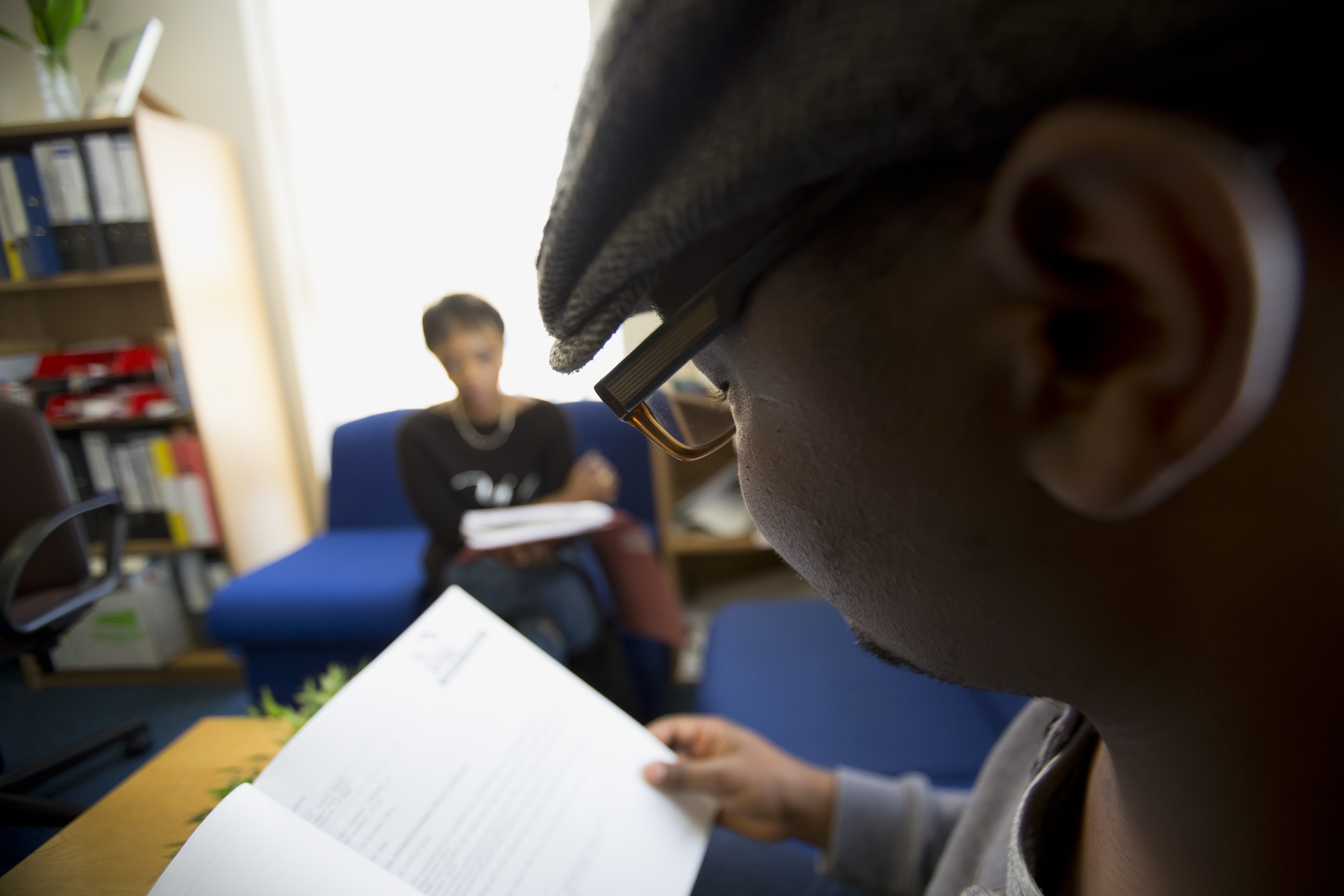 Picture of a man looking at paperwork in a meeting with a Refugee Action advice worker.