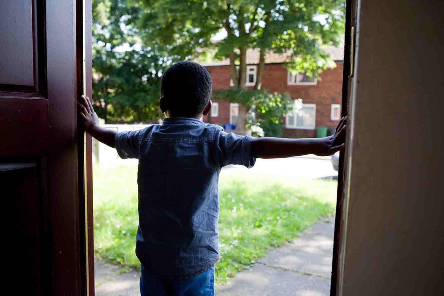young boy holding open a door and looking out at a bright day