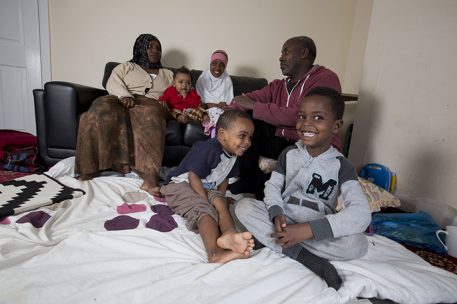 A refugee family sit in their living room in the UK. Mum and dad sit on the sofa with their baby daughter and elder daughter. Their two young sons sit on the floor; one brother is laughing at the other, who is smiling at the camera with a cheeky grin.