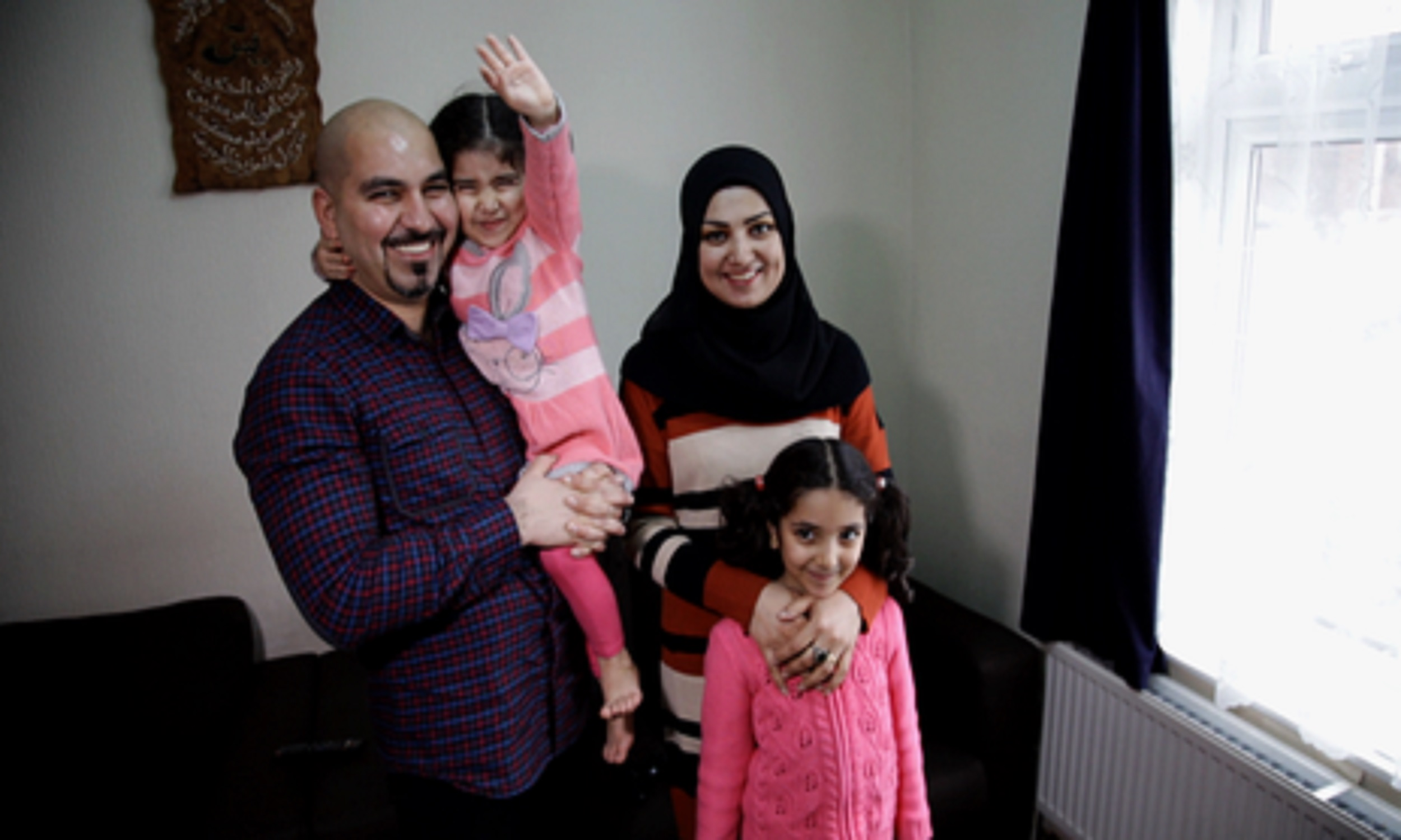 Haider, a refugee from Iraq with his wife and two daughters in their living room