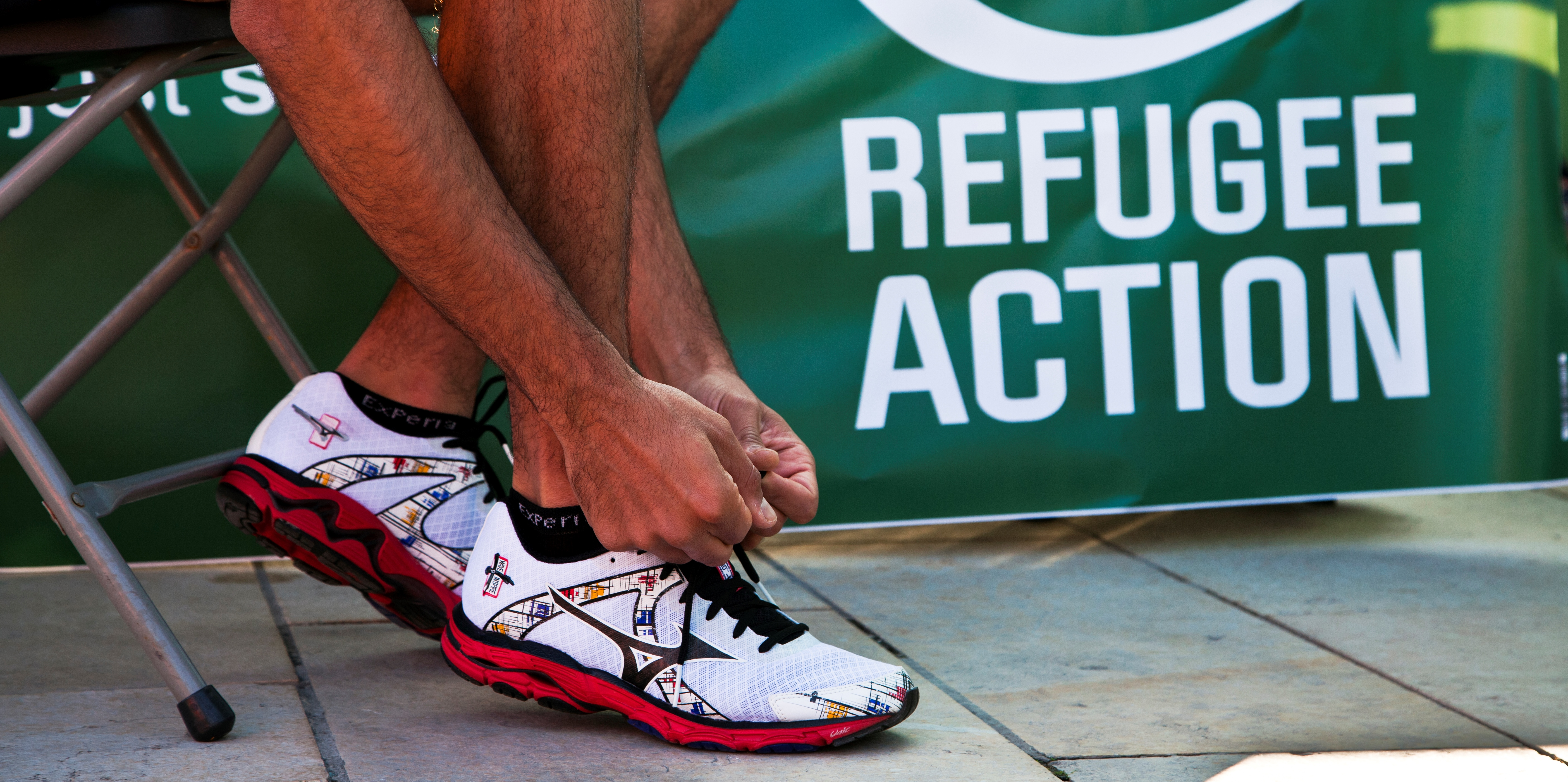 Close-up of a Refugee Action event participant tying his shoelaces.