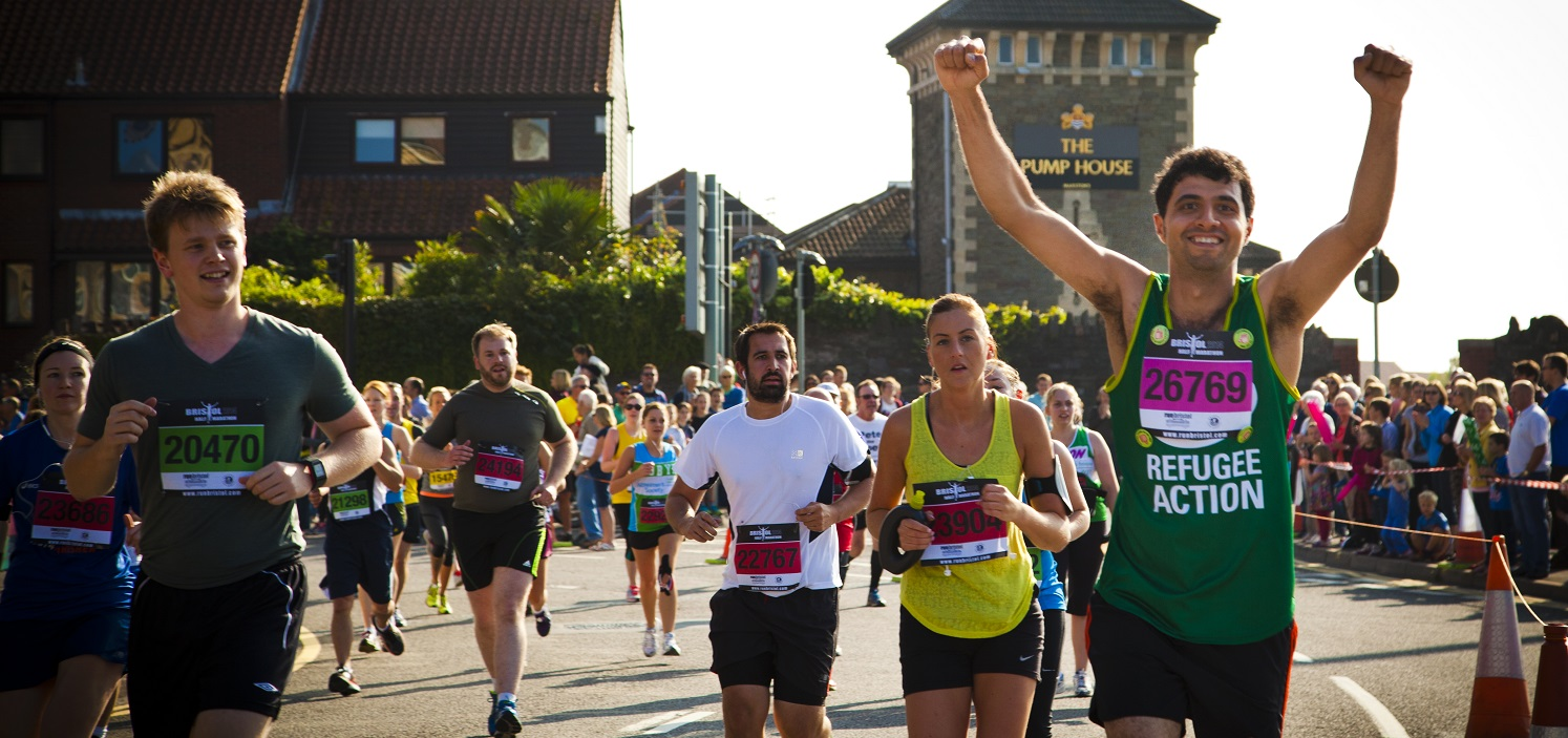 A runner in a Refugee Action vest runs a race