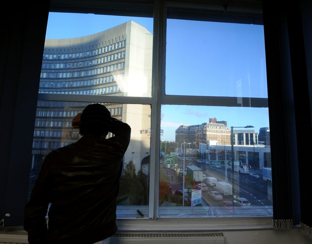 Man looking out of window at city landscape