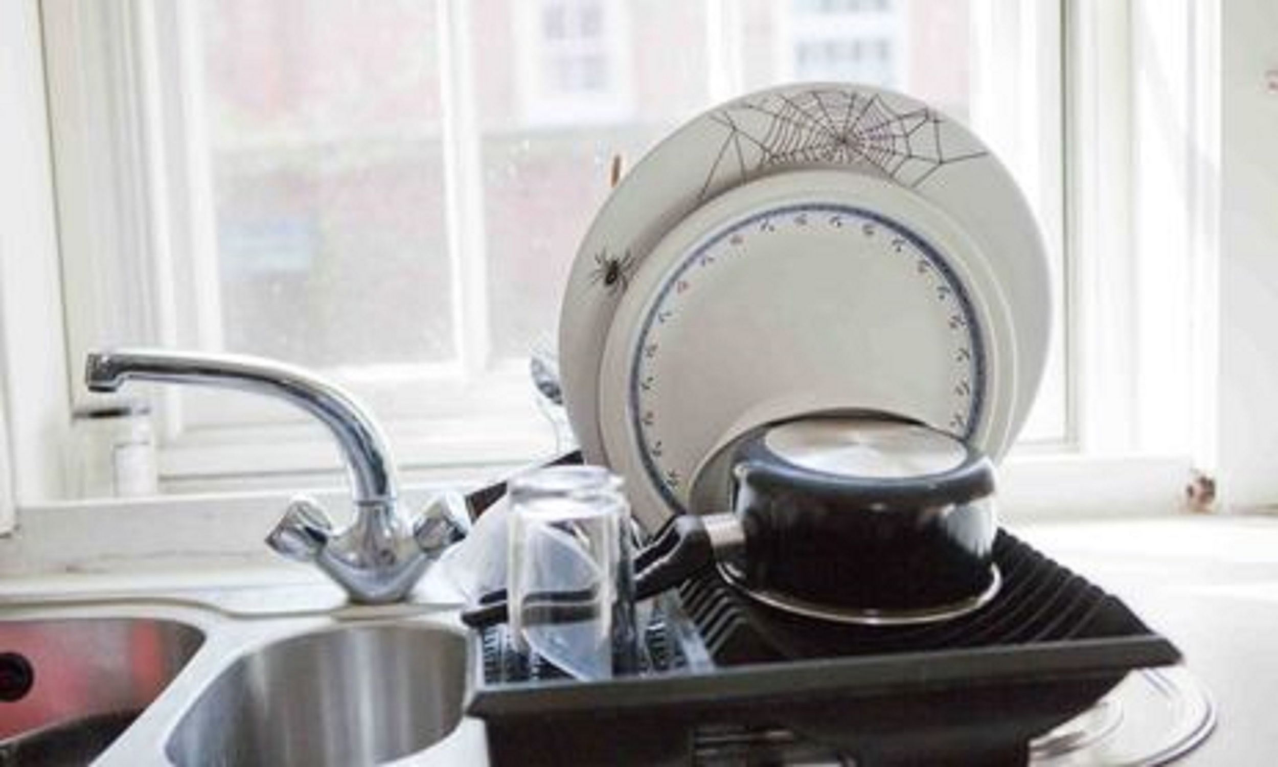 Photo of clean dishes drying beside a sink