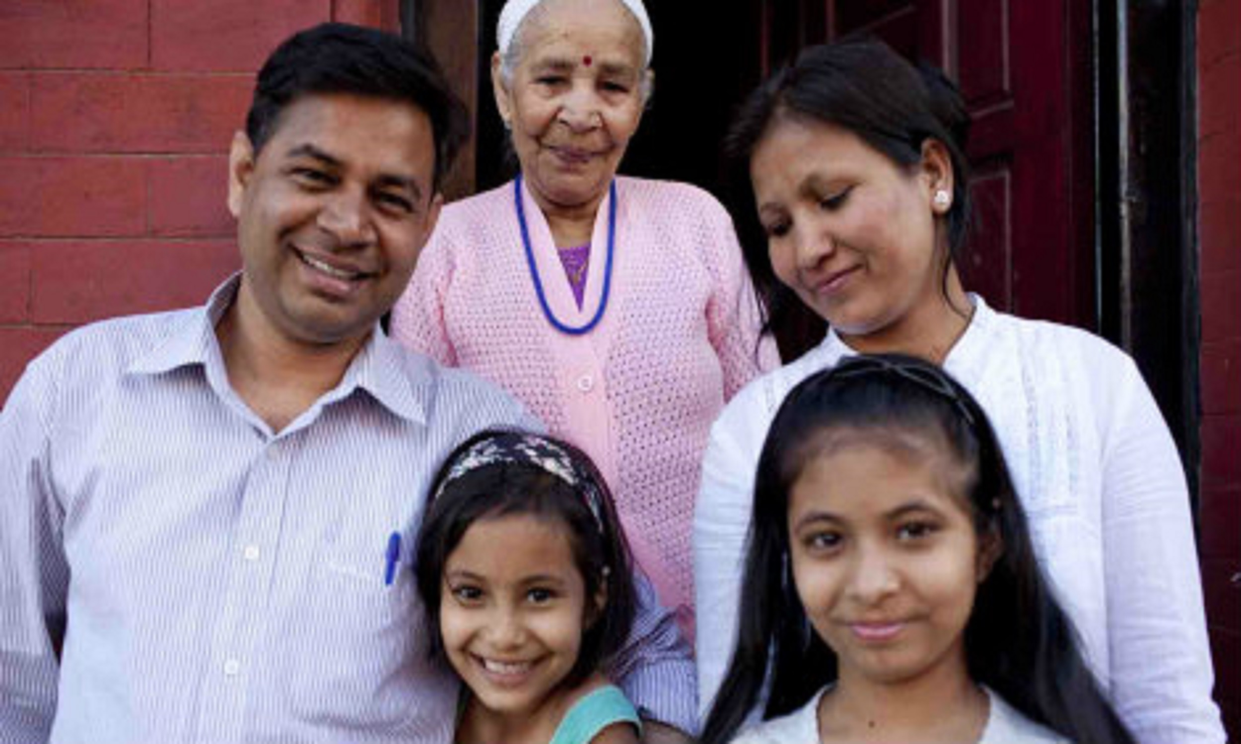 Prem, a refugee from Bhutan, with his family outside his house