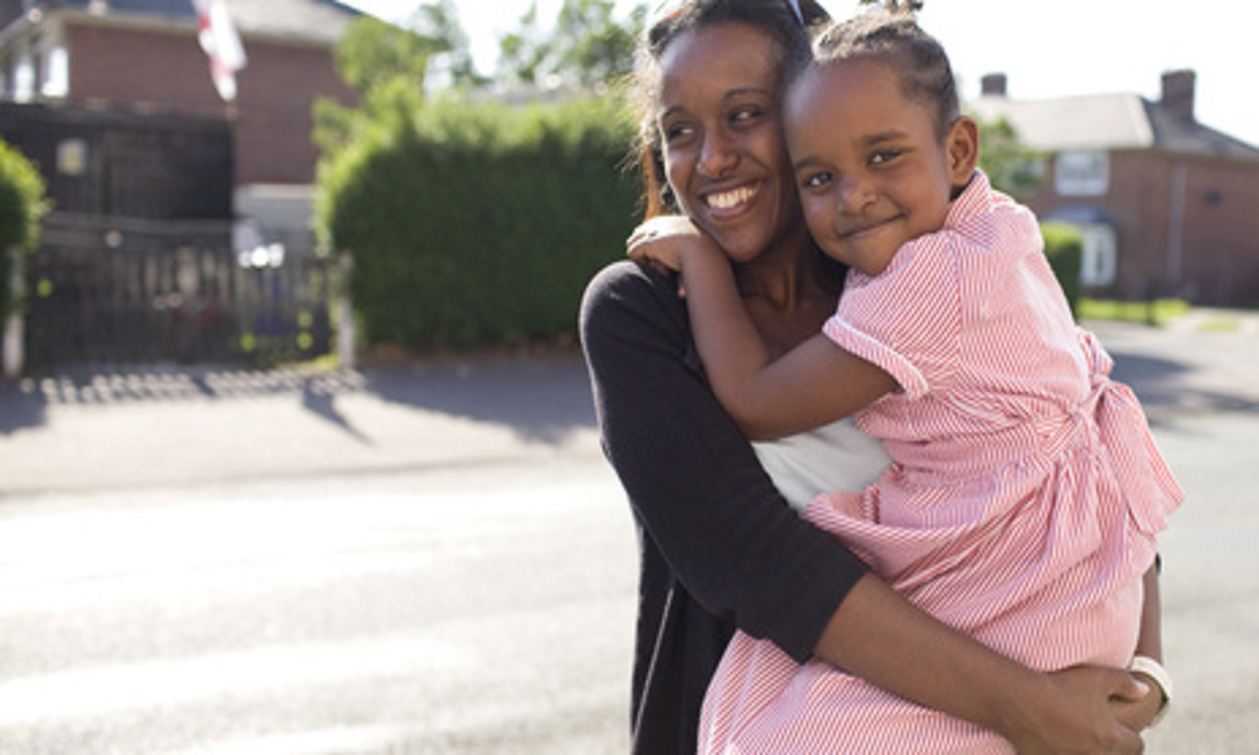 Photo of Sisay, a refugee from Eritrea, with a young girl in her arms