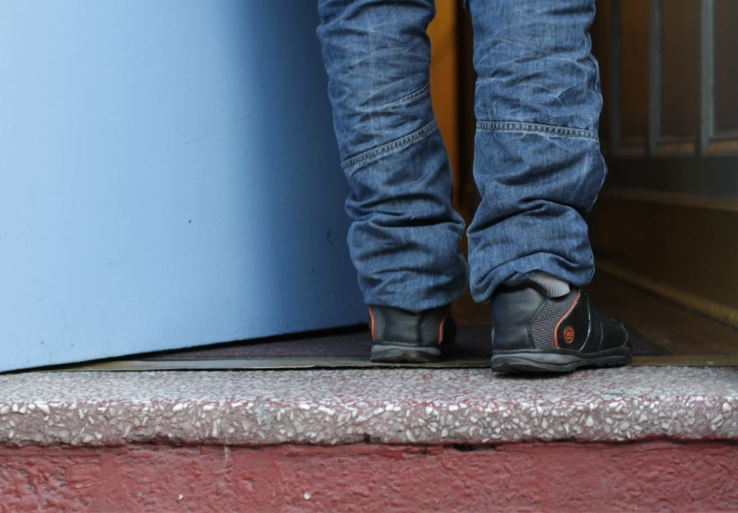 Picture of a young man's feet as he walks through a doorway.