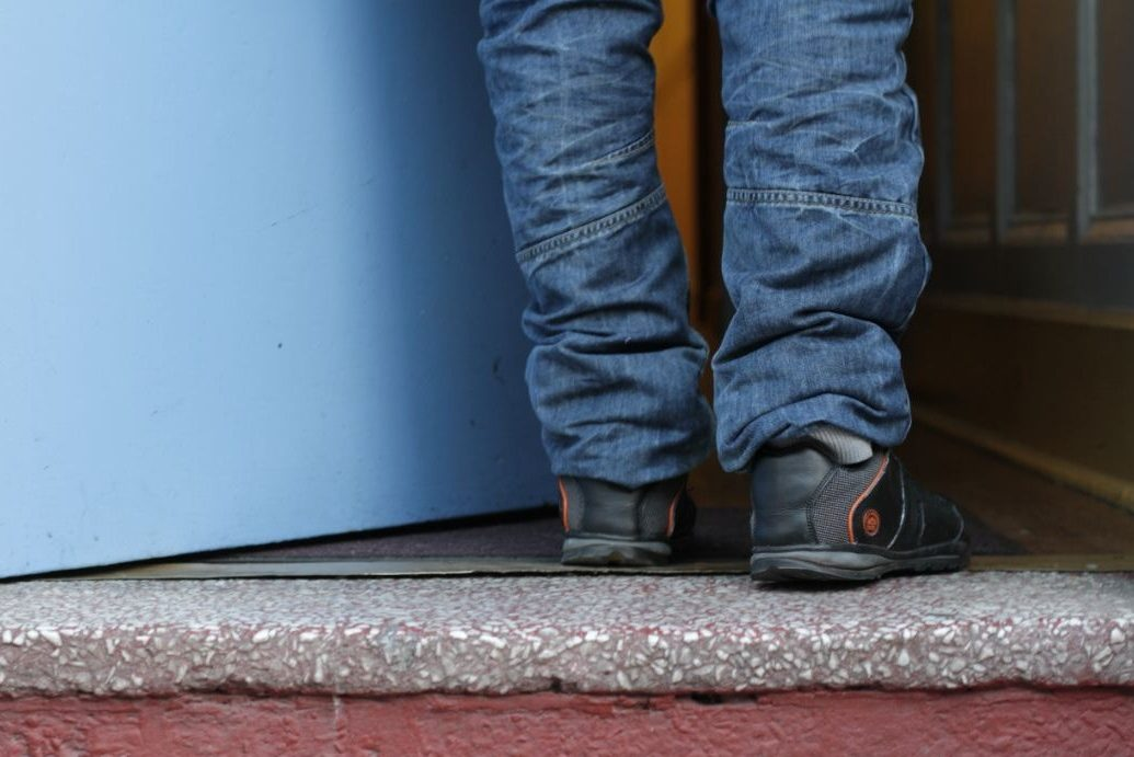 Picture showing a young refugees feet as he walks through a doorway.