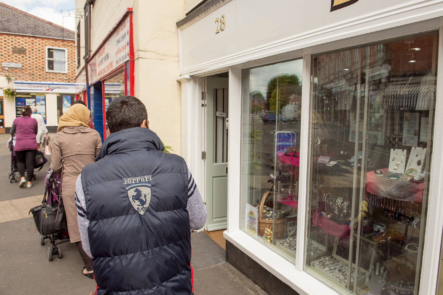 A Syrian refugee family walks past a shop window in an English town. The wife is pushing a young child in a pushchair.