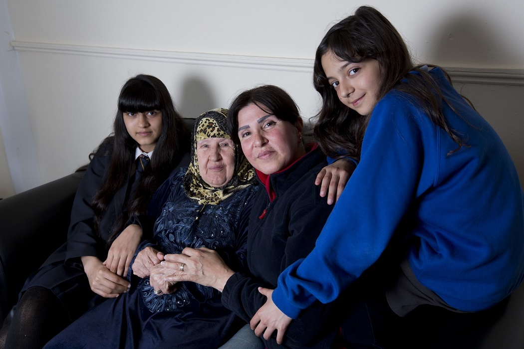 Ban, a single mother who fled wars in Iraq and Syria, sits on a sofa with her two daughters and her elderly mother.