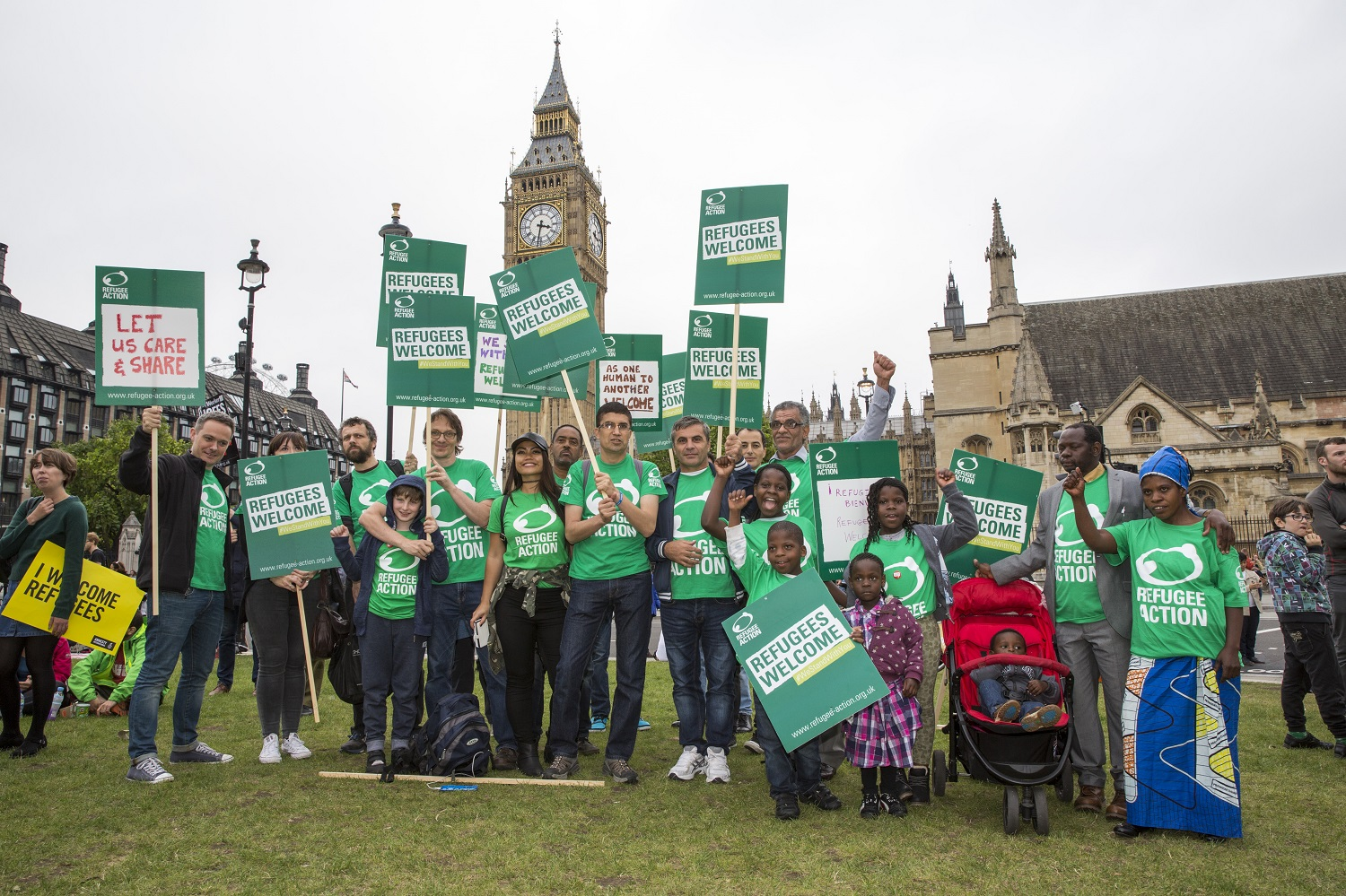 Wearing bright green t-shirts and carrying banners proclaiming messages of welcome and support for other refugees, members of Refugee Action's Refugee and Asylum Seeker Voice group stand in front of Big Ben at the London Refugees Welcome March in September 2016.