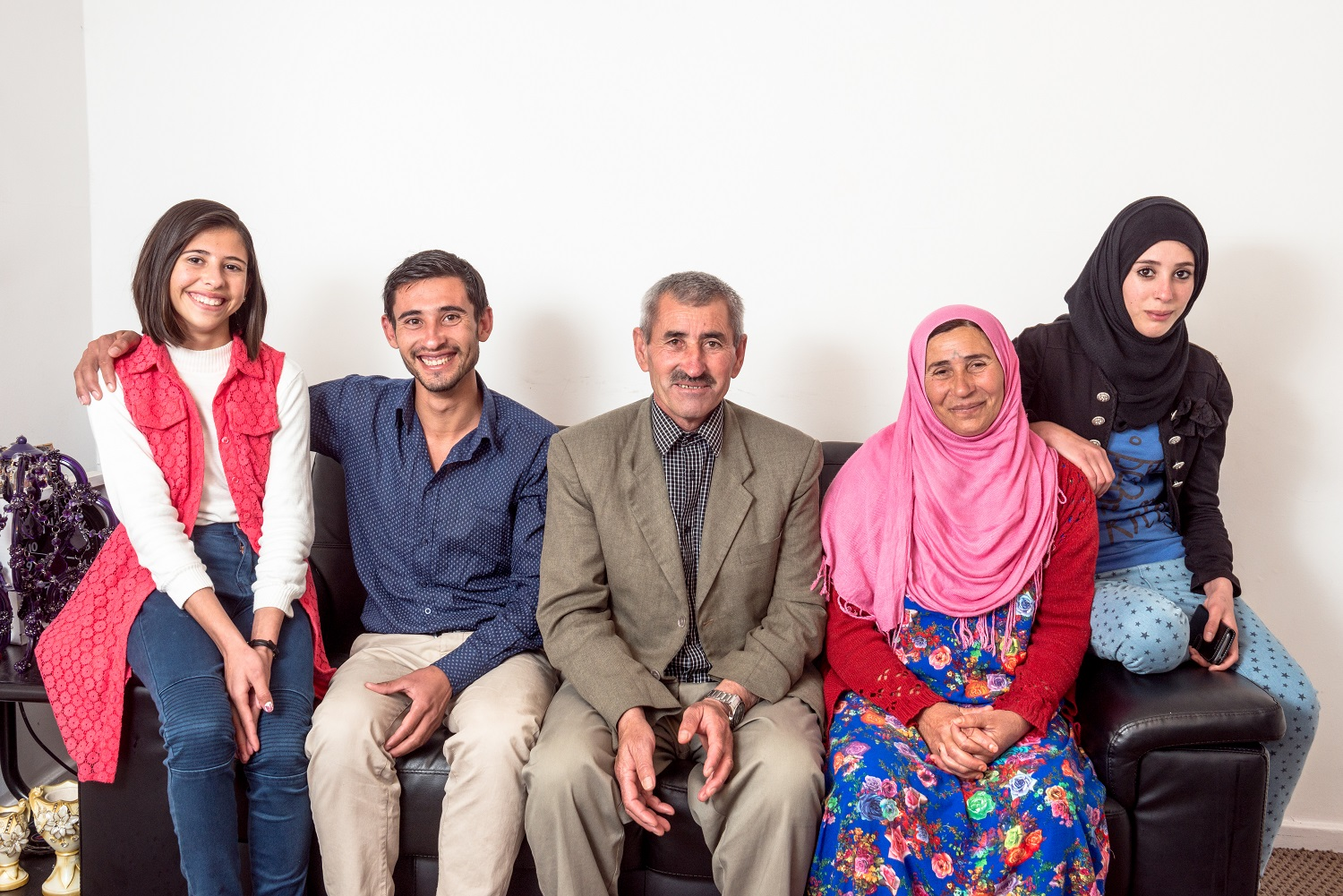 A Syrian refugee family sit on a sofa in their new home in the UK. On the far left sits their youngest daughter who is twelve. Next to her is their son is twenty-one. Then there is the father and mother, followed by the older daughter who is sixteen. The family are smiling and looking hopeful.