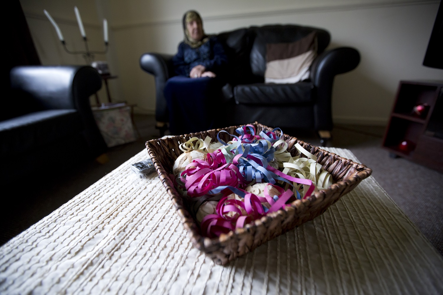 A elderly refugee woman, resettled to the UK after fleeing war in Syria, sits peacefully on a sofa in her new home. In the foreground is a bowl of brightly coloured paper decorations.