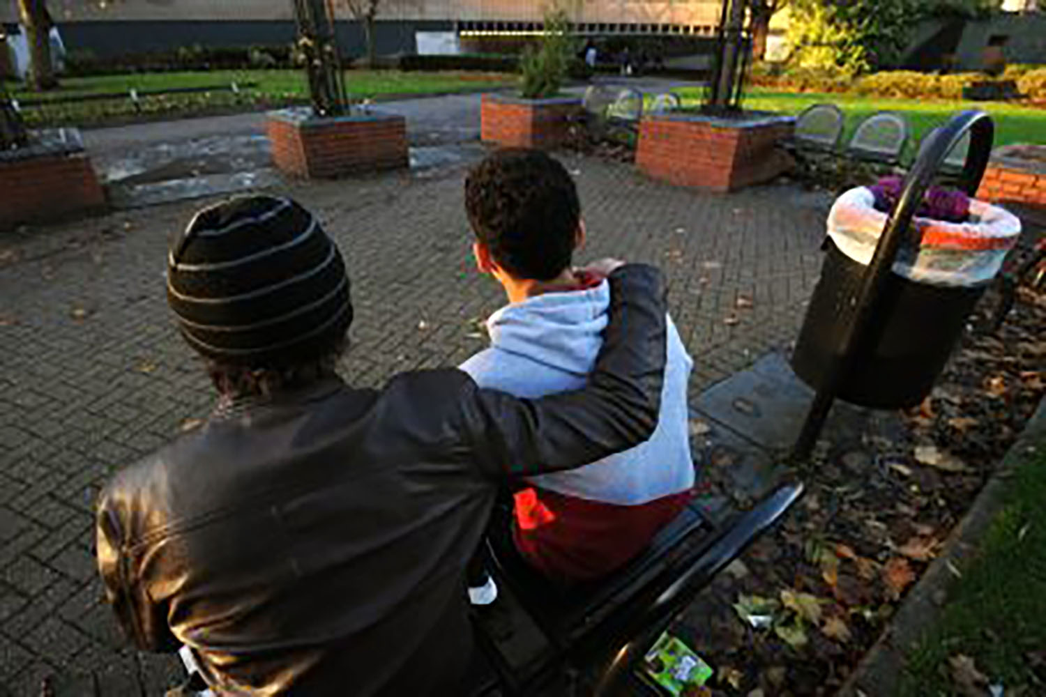 two young men sitting on a bench one with an arm around the other