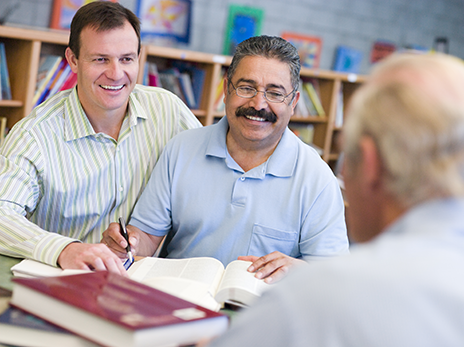 Three men attend an English language class. Two are facing the camera, looking at open books, and smiling. One is facing away from the camera and appears to be the class teacher.