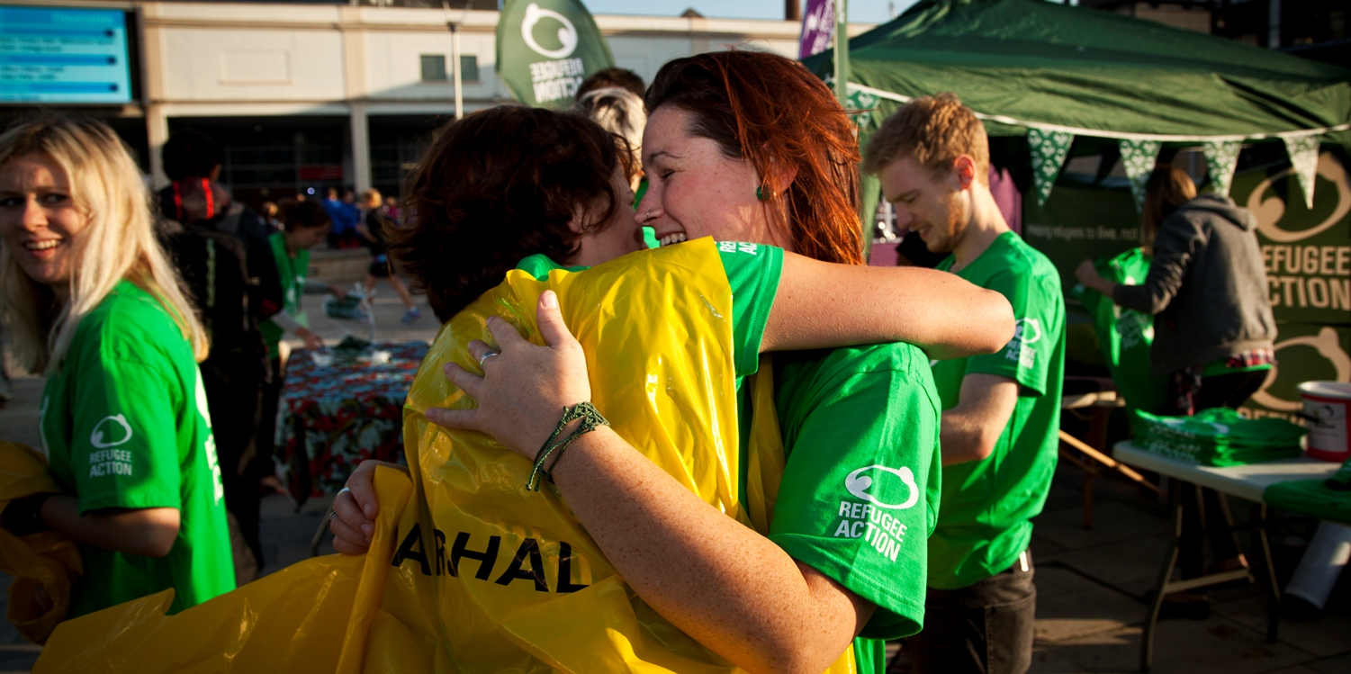 Smiling woman wearing Refugee Action green T-shirt is hugging another person wearing a yellow vest