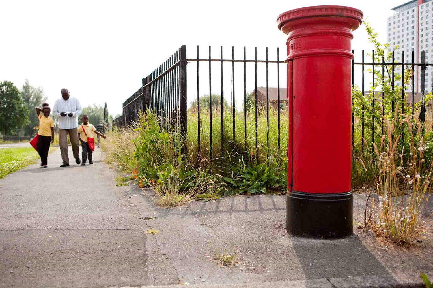 A refugee man and his two young children walk home from school. In the foreground ahead of them is a bright red British postbox.