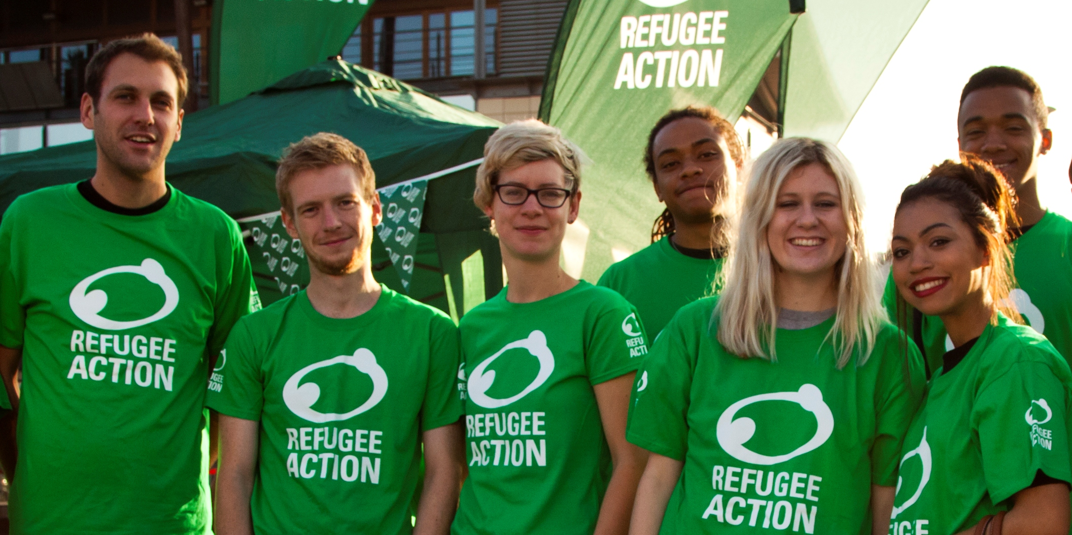 a group of smiling young people wearing a green refugee action t-shirt in the afternoon