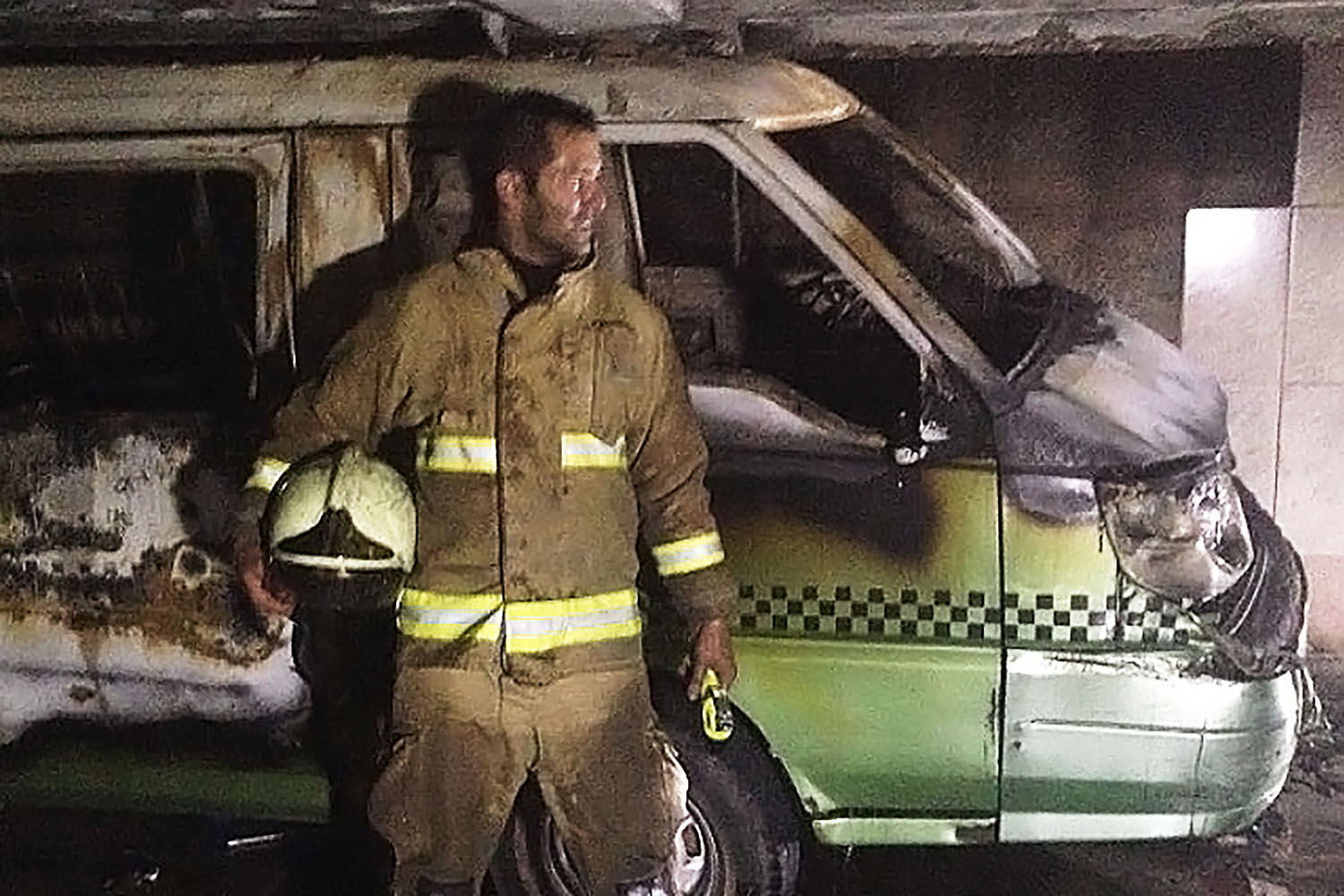 Photo of Mohsen, a refugee from Iran, at work as a firefighter in Iran. He is standing in his uniform in front of a burned out ambulance, covered in soot.
