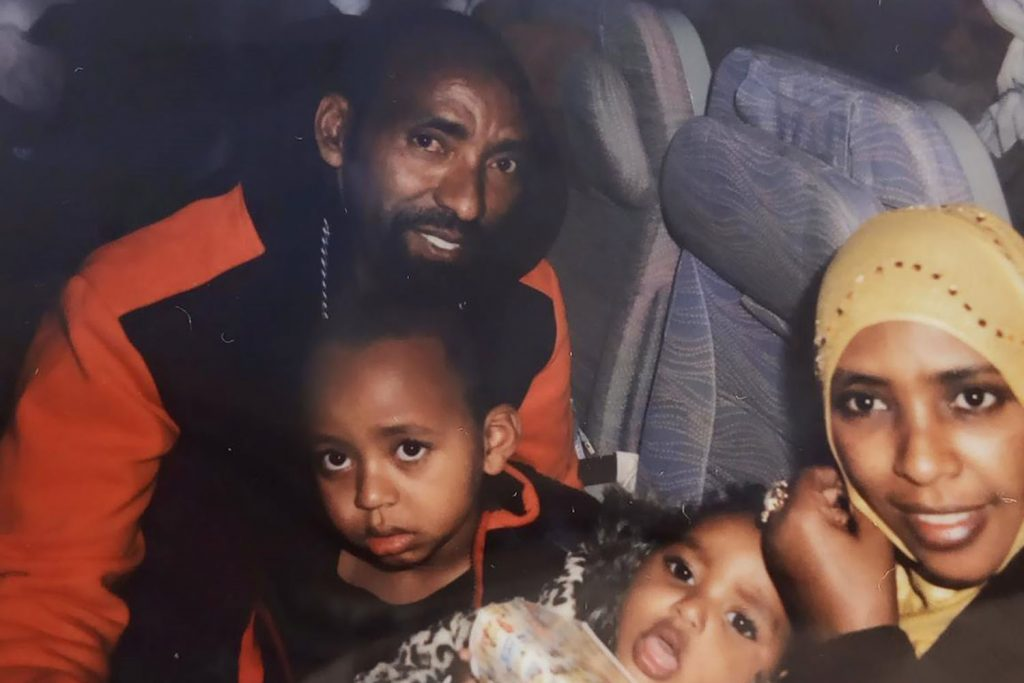 Photo of Ethiopian refugee Siraje, with his wife and two daughters, sitting together on an airplane.