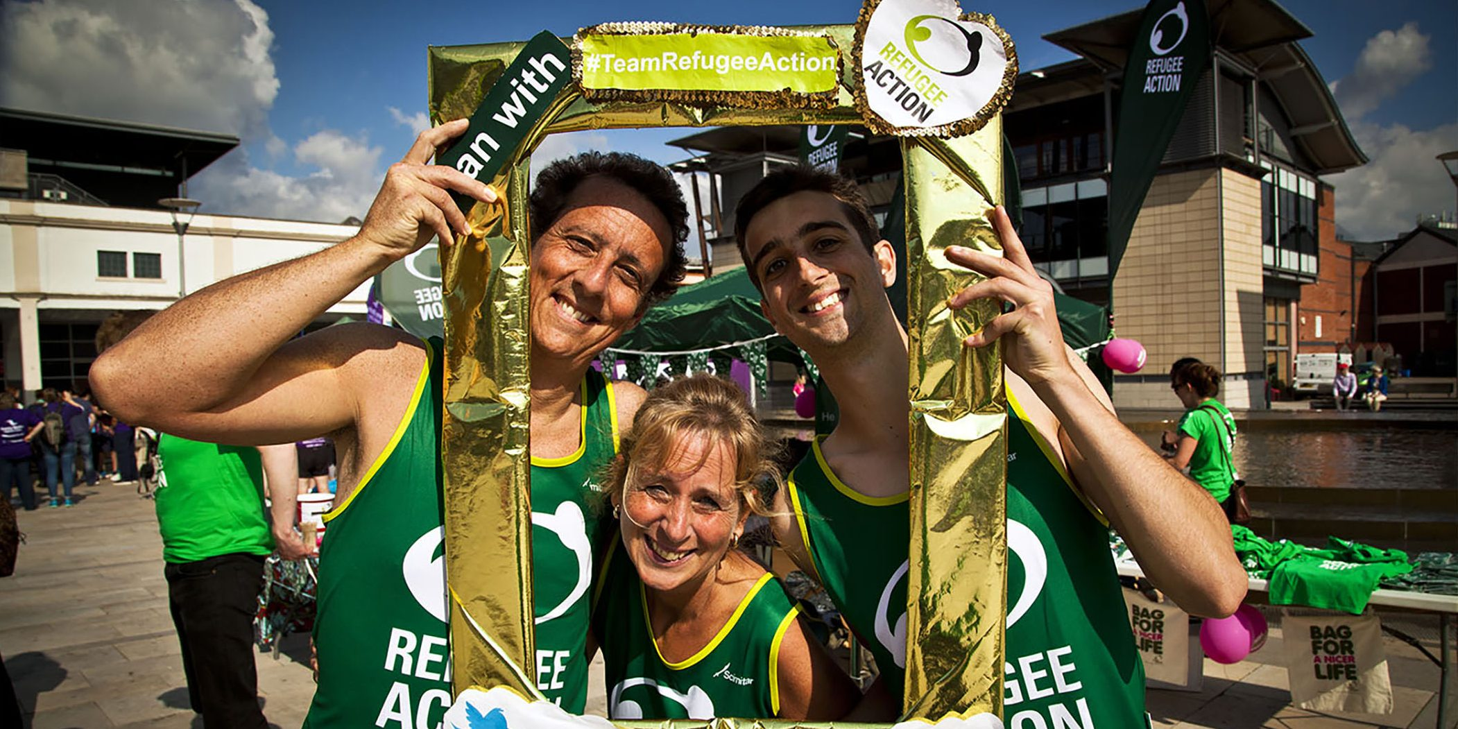 three runners in refugee action vests posing for a photograph holding a golden picture frame