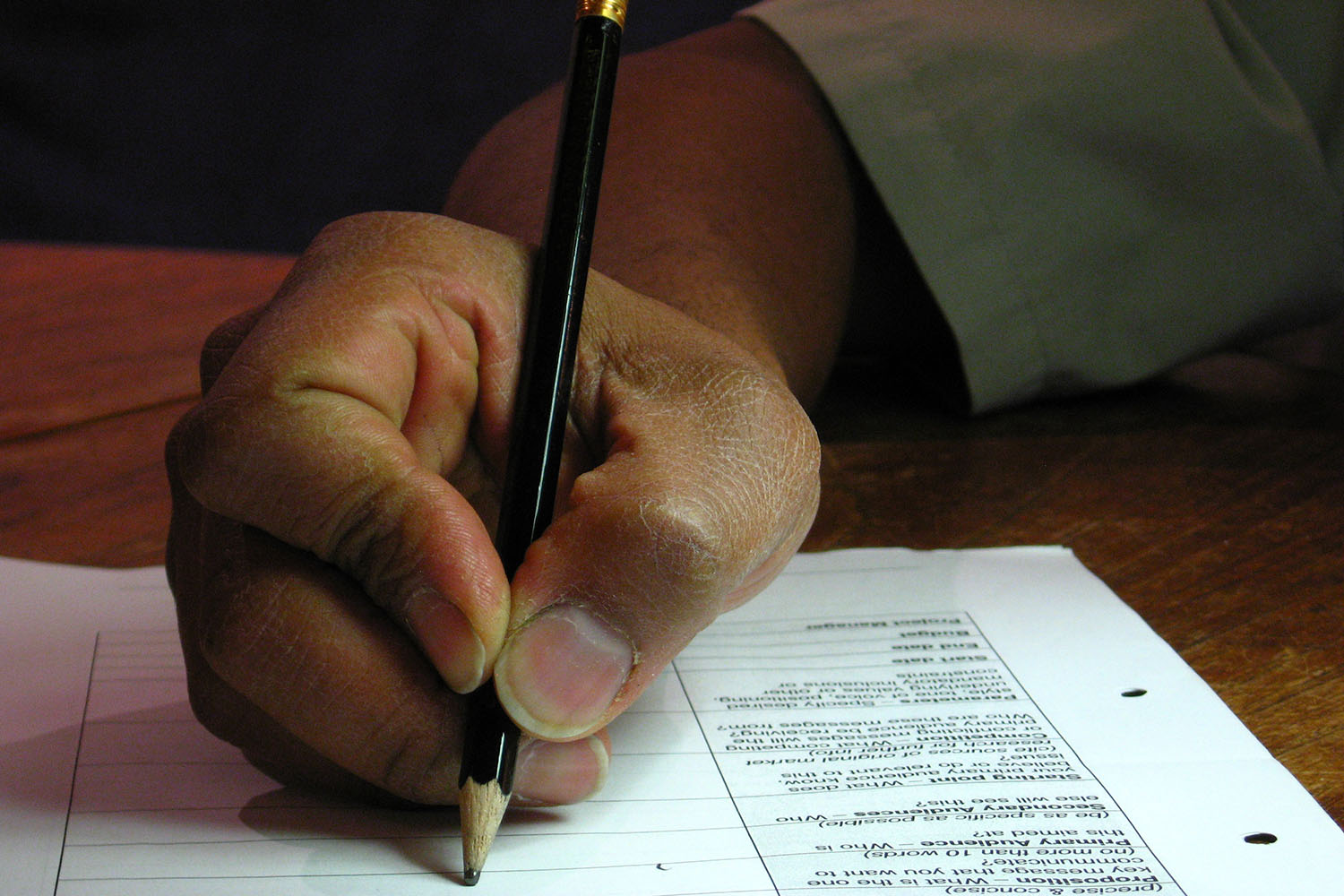 Close up of man's hand filling in a form with a pencil. Refugee Action Voluntary Return Good Practice Project