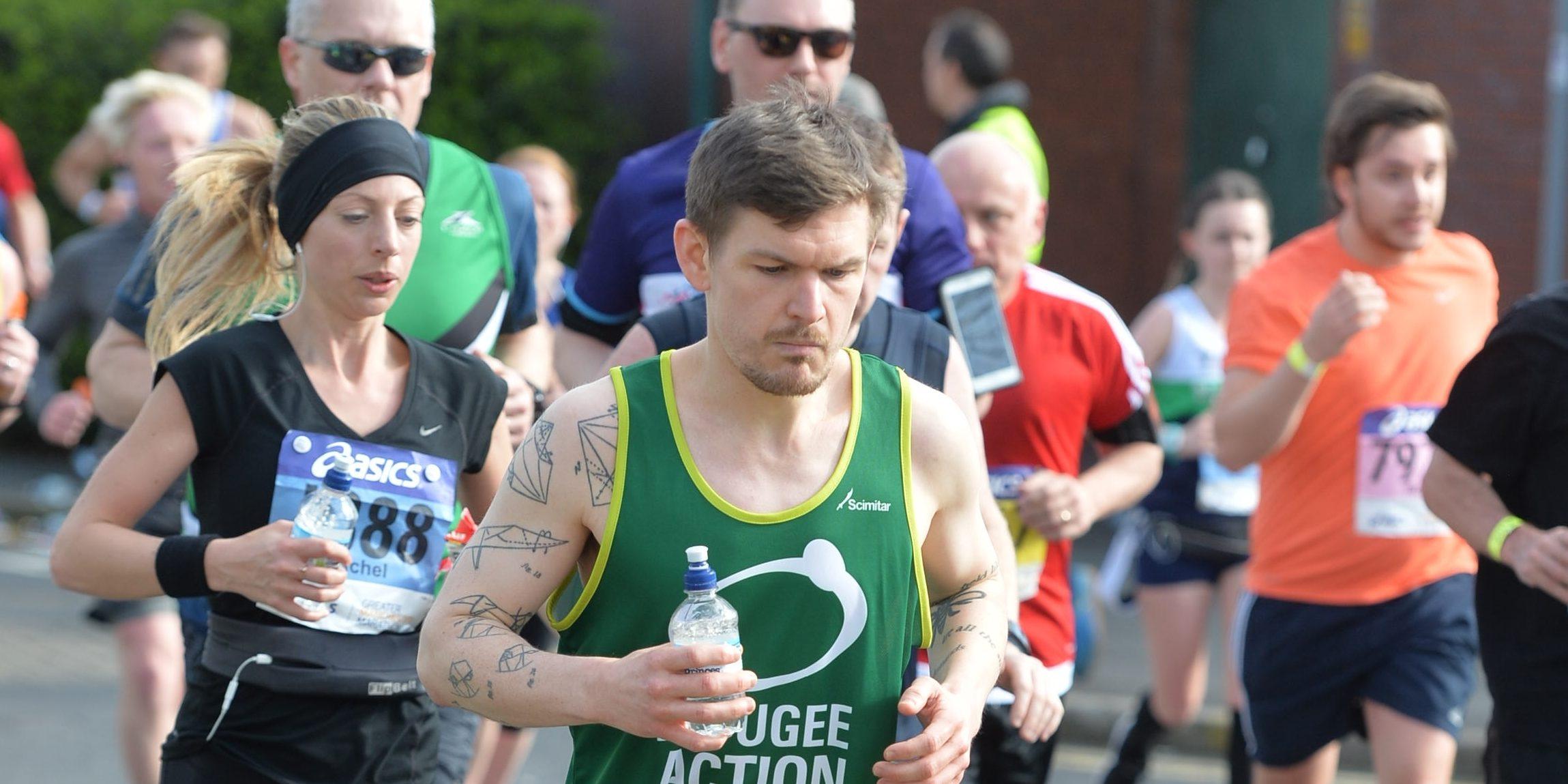 a man wearing a Refugee Action vest running a race