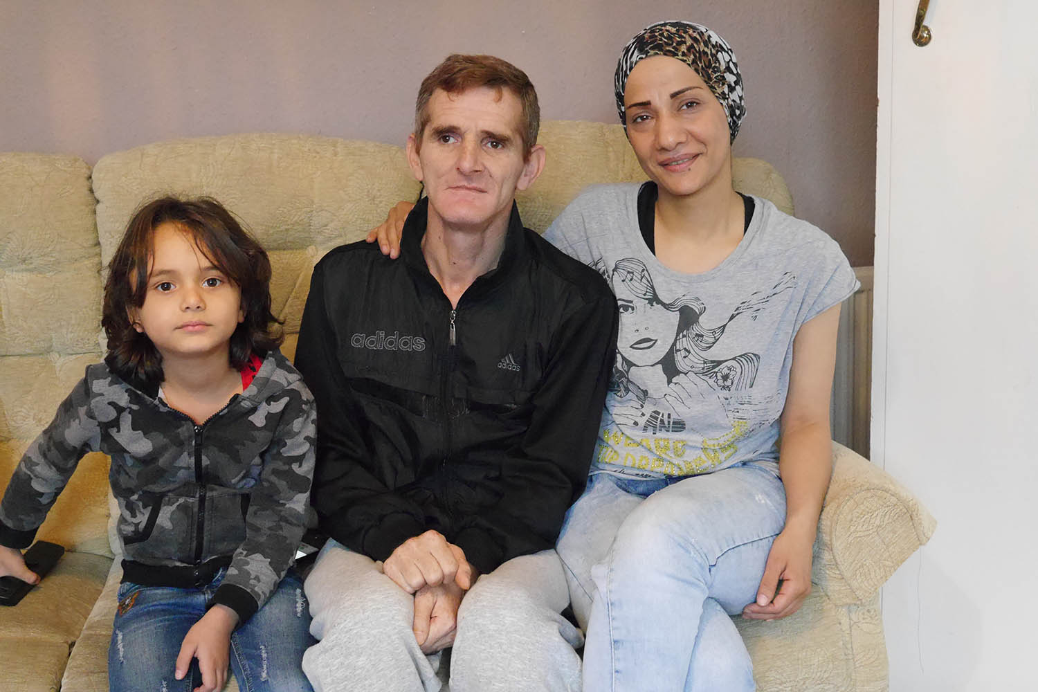 Refugees from Syria Mountaha and Ahmad at home with their son