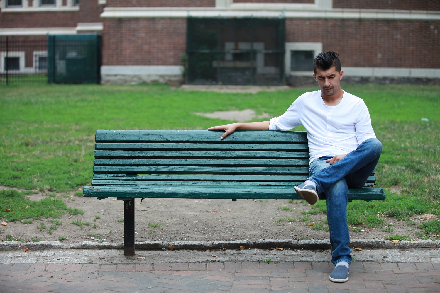 A man in a white long-sleeve t-shirt and jeans sits on a bench, looking down at his phone.
